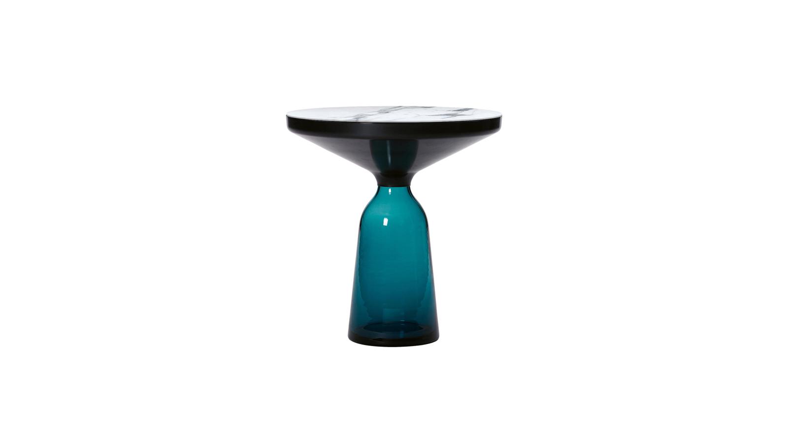 Sebastian Herkner Bell asztala feje tetejére állítja az anyaghasználat hagyományait. A törékenységet, könnyedséget előhívó üveg a Bell esetében tartóelemként funkcionál egy hagyományosan nehezebb anyag, a fém alapjaként. Paradox módon kifordítottsága harmóniát és stabilitást sugároz. A Bell az anyagok és a színek szépségét ünnepli, szobrászati műként lebeg a térben - egy sajátos kézműves darab a kiválóság jegyében.