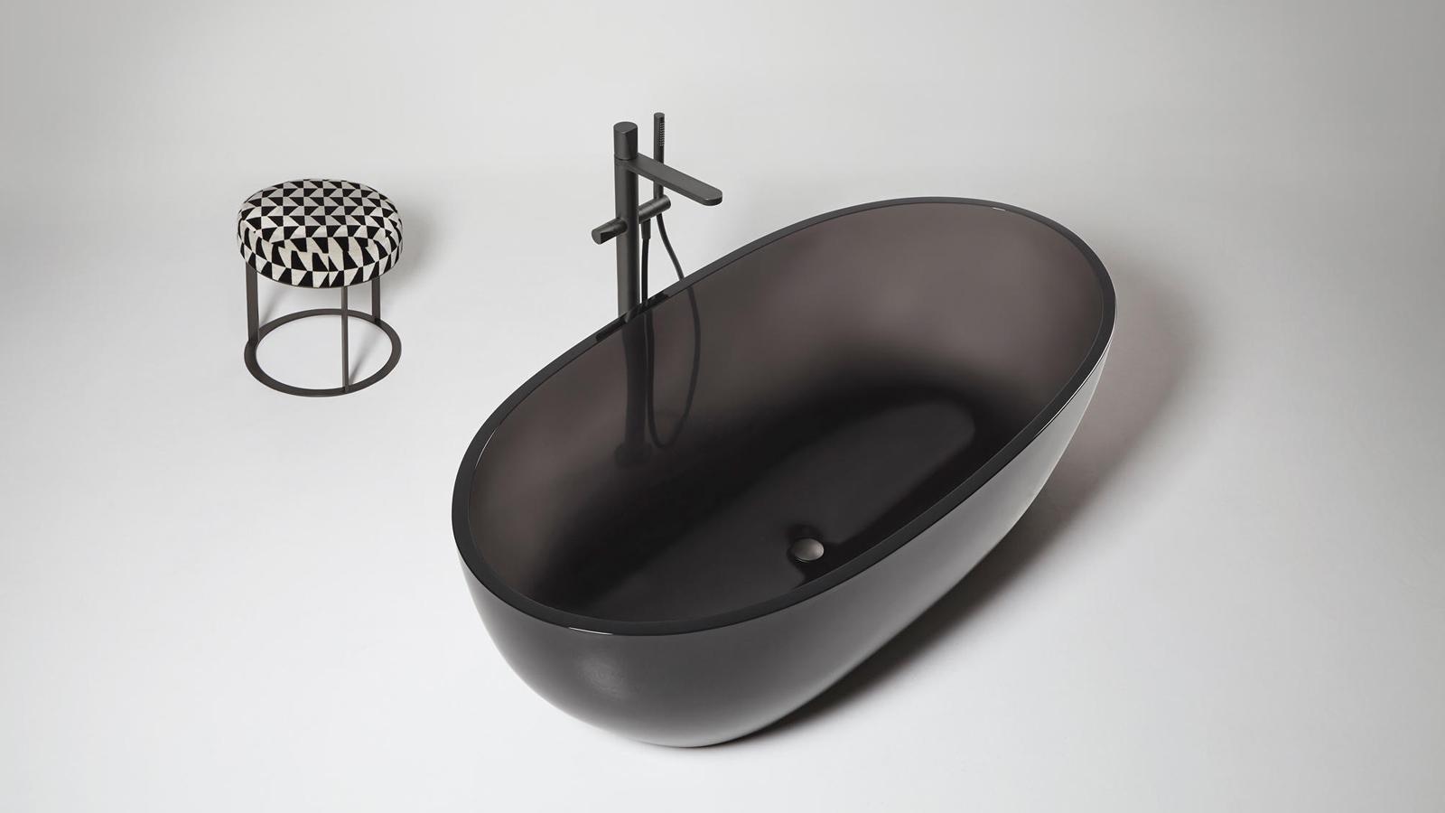 Az antoniolupi Reflect kádja sajátos technikai karakterrel bír - a tervezést megelőző kutatási folyamatnak köszönhetően egy olyan anyagot fejlesztettek, amely nem csak ránézésre, de fizikailag is egy könnyű anyagot hoz létre. Az ívelt, lágy formavilág és a könnyű anyag kettőse meleg, meghitt teret biztosít a fürdéshez, transzparenciájával pedig a víz főszerepét adja vissza. A kissé áttetsző anyag ugyanis lehetővé teszi, hogy a víz áramlása, mozgása megfigyelhető legyen a kádon kívül is. Az önmagában is markáns elem a csapot megnyitva vibráló, élettel teli szereplője lesz a fürdőszobának - így válik a fürdés vizuális élménnyé.