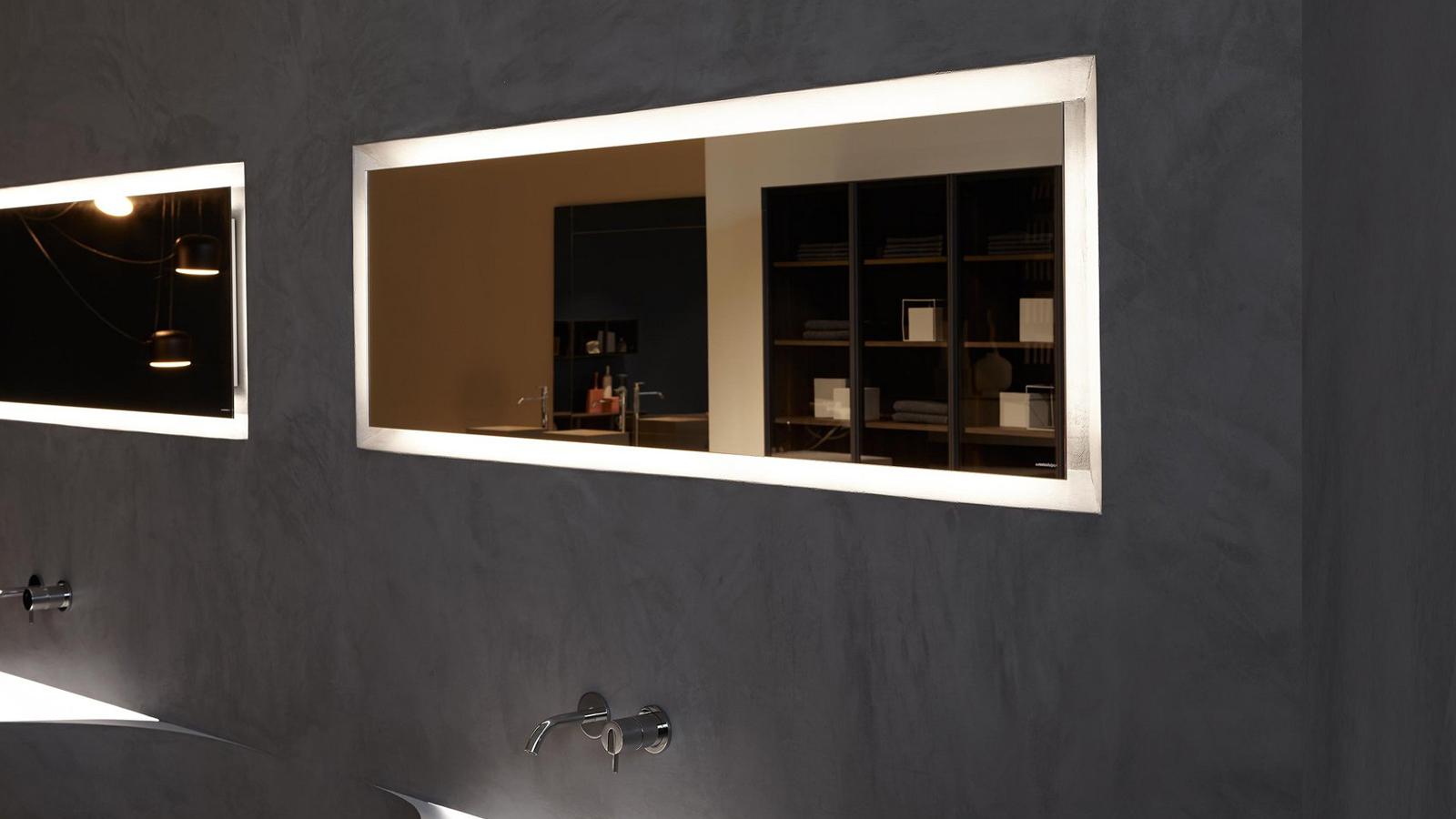 Világító képkeret, vagy falba süllyesztett tükör?... a Periplo mindkettő: egyszerű, négyszögletes tükördarab, körbefutó LED-világítással, melyet a mögötte elhelyezkedő mélyedés hangsúlyoz még tovább. A fény és a mélységek játékából létrejött, különleges darab függőlegesen és vízszintesen is felhelyezhető.