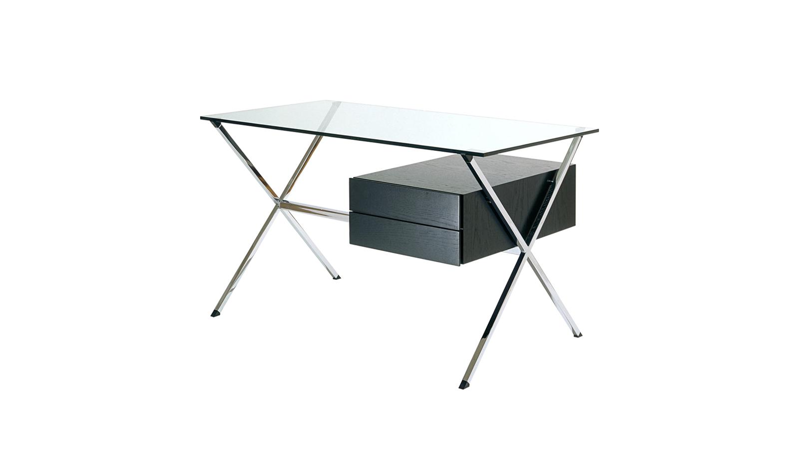 Franco Albini 1928-as, emblematikus asztala fémet, üveget és fát ötvöz egy tiszta szerkezetben, ahol nincs egyetlen felesleges vonal sem. A fém vázszerkezet az oldalakon x-alakban nyílik lábakká, melyek köz egy összekötő rúd úgy tartja a kis fiókos elemet, mintha lebegne. Az asztal hűen tükrözi Albini racionalista designját, pontos egyensújt tartó, minimalista filozófiáját, ahol a maga az anyag, az alkotó elem kerül reflektorfénybe.