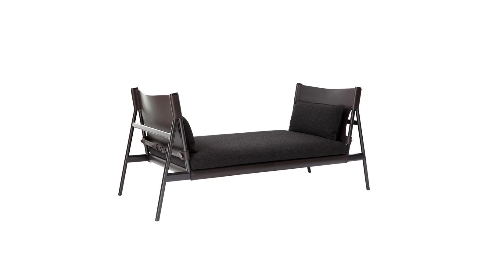 """""""A Porro Traveller darabja elegáns és eredeti, szimmetrikus, arányos és kényelmes. A fekete fém tartószerkezet a kárpit és a párnák tartójaként szerepel, amellett, hogy a formavilágát is definiálja a darabnak. Nyeregszerű bőrhatása robosztusságot hoz létre, ám az összkép mindvégig lágy marad a két szövetpárna jelenlétének köszönhetően. A bútor variábilis: kárpitozott elemei könnyen eltávolíthatóak és cserélhetőek. A megnyújtott ülőpárna rész kényelmes pozíció felvételére ösztönzi használóját, ideális gardróbokban elhelyezve. """""""