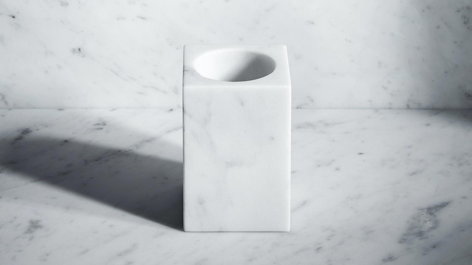 Egyetlen darab természetes kőből készült ez a rendkívül elegáns, letisztultságával hódító fogkefetartó. A négyzetes befogadó forma és a kerek belső ív kontrasztja kivételesen harmonikusan összképet eredményez. A termék, mely végső formáját kézműves mesterek munkája által nyeri el, kétféle anyagból érhető el. A Fontane Bianche sorozat Elisa Ossino formatervező alkotása.